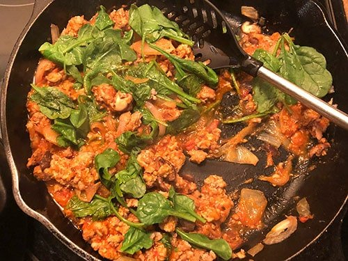 making a quick pasta sauce in the skillet with turkey, tomato sauce and spinach.