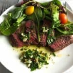 roasted steak with chimichurri sauce and salad on a plate.
