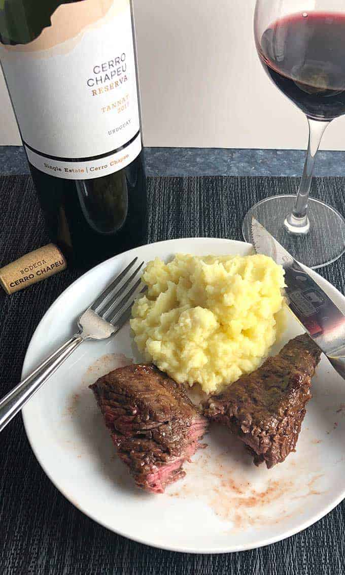 BBQ baked steak tips on a plate with mashed potatoes and red wine.