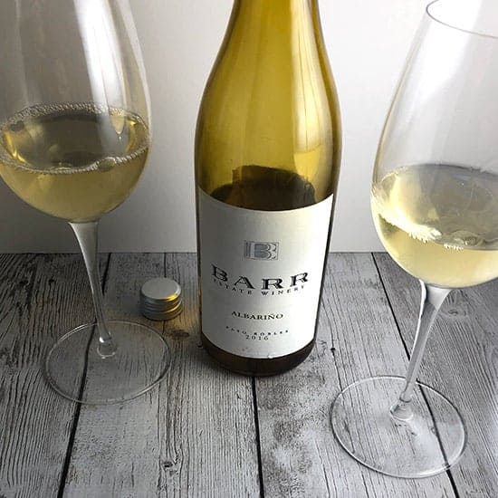bottle of Barr Estate Albariño with two glasses of white wine.