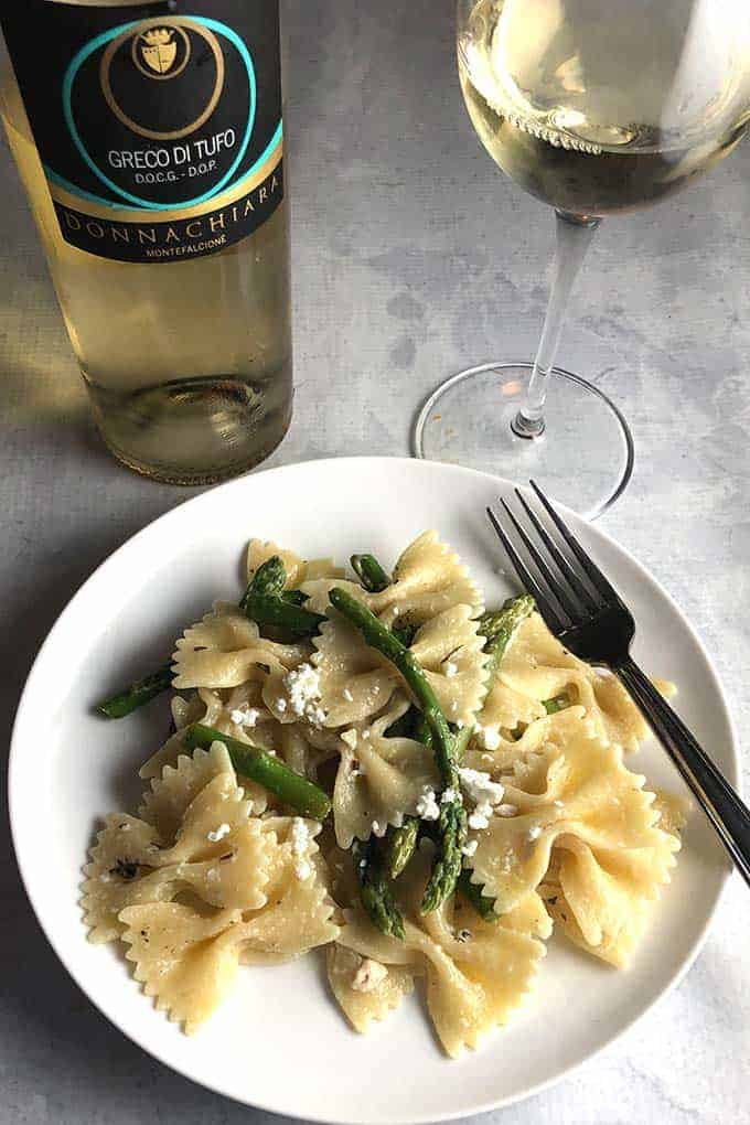 a plate of asparagus goat cheese pasta with a bottle of white wine.