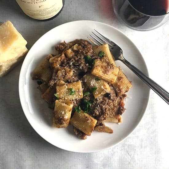 mushroom and short rib ragu on a plate serve red wine on the side.