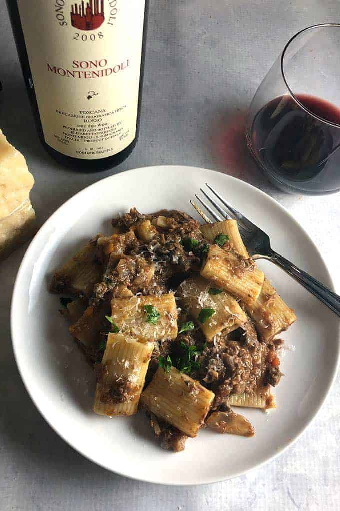 Short Rib Ragu on a plate, served with red Italian wine.
