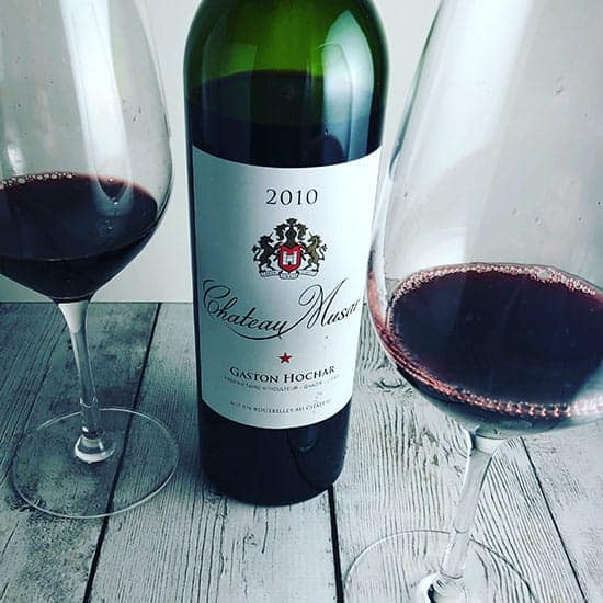 bottle of Chateau Musar red wine with two glasses poured.