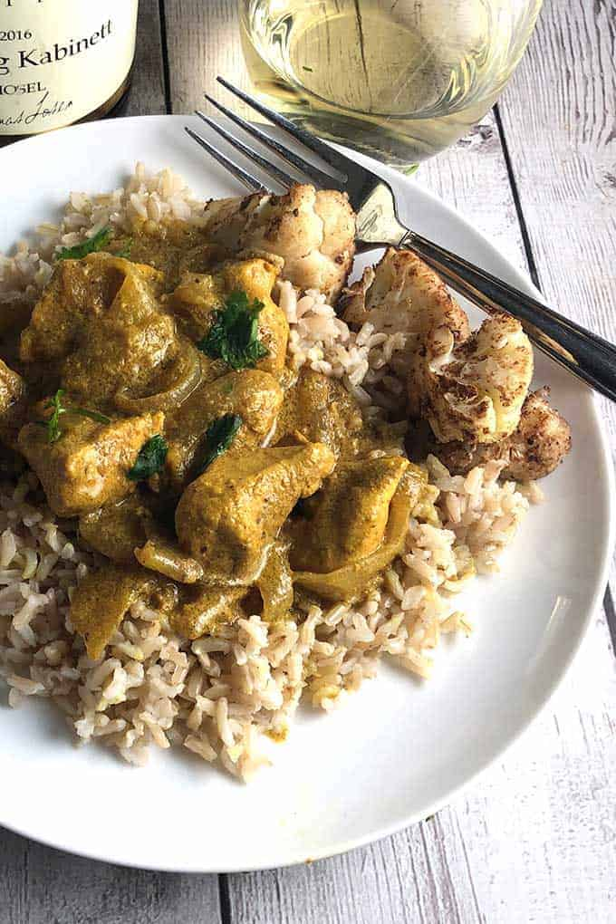 Indian Butter Chicken served with cauliflower and white wine.