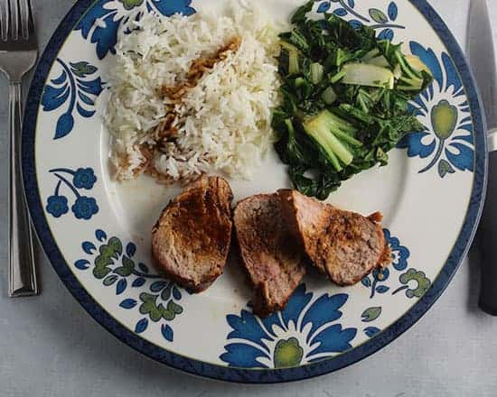 Asian Grilled Pork Tenderloin on a plate with bok choy and rice.