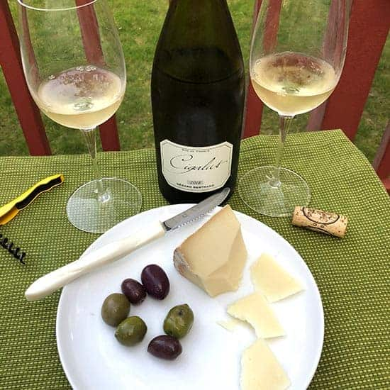 Cigalus Blanc wine with a plate of cheese and olives.