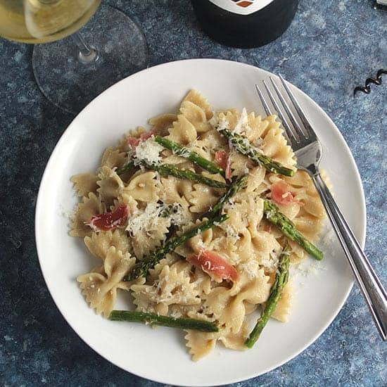 roasted asparagus pasta on a plate with white wine.
