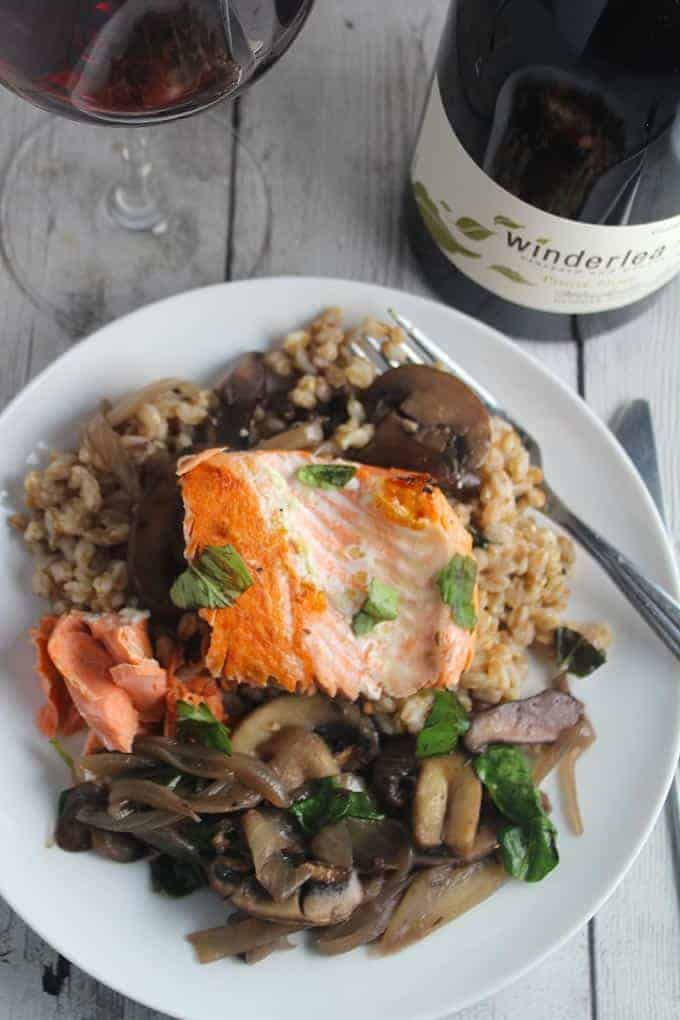 salmon with farro and mushrooms on a plate, served with Pinot Noir.