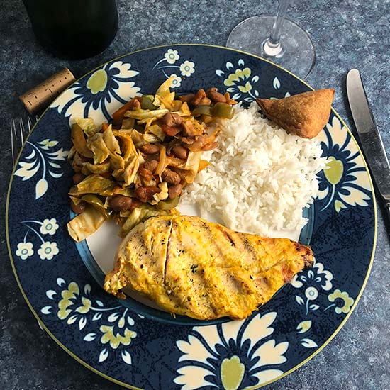 south african chicken on a plate with chakalaka and rice.