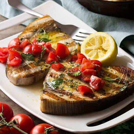 Grilled Sicilian Swordfish plated with tomatoes