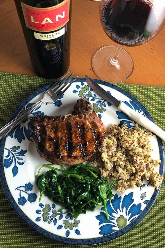 Paprika pork chops plated with spinach and quinoa with Rioja wine.