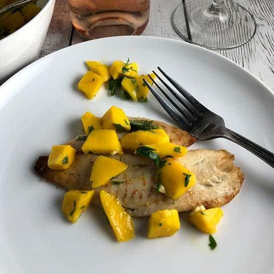 tilapia plated with mango salsa.