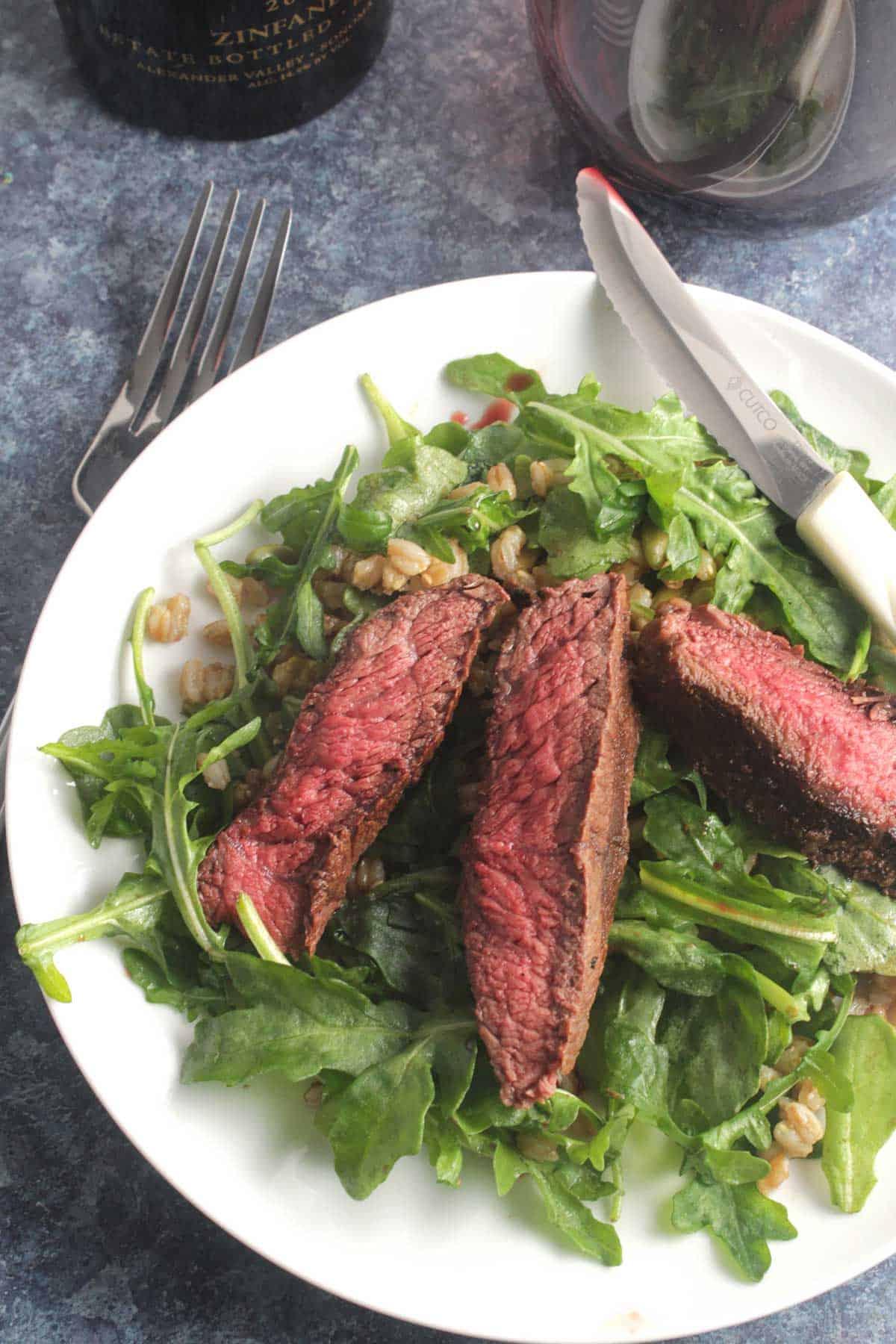arugula and steak salad on a white dish.