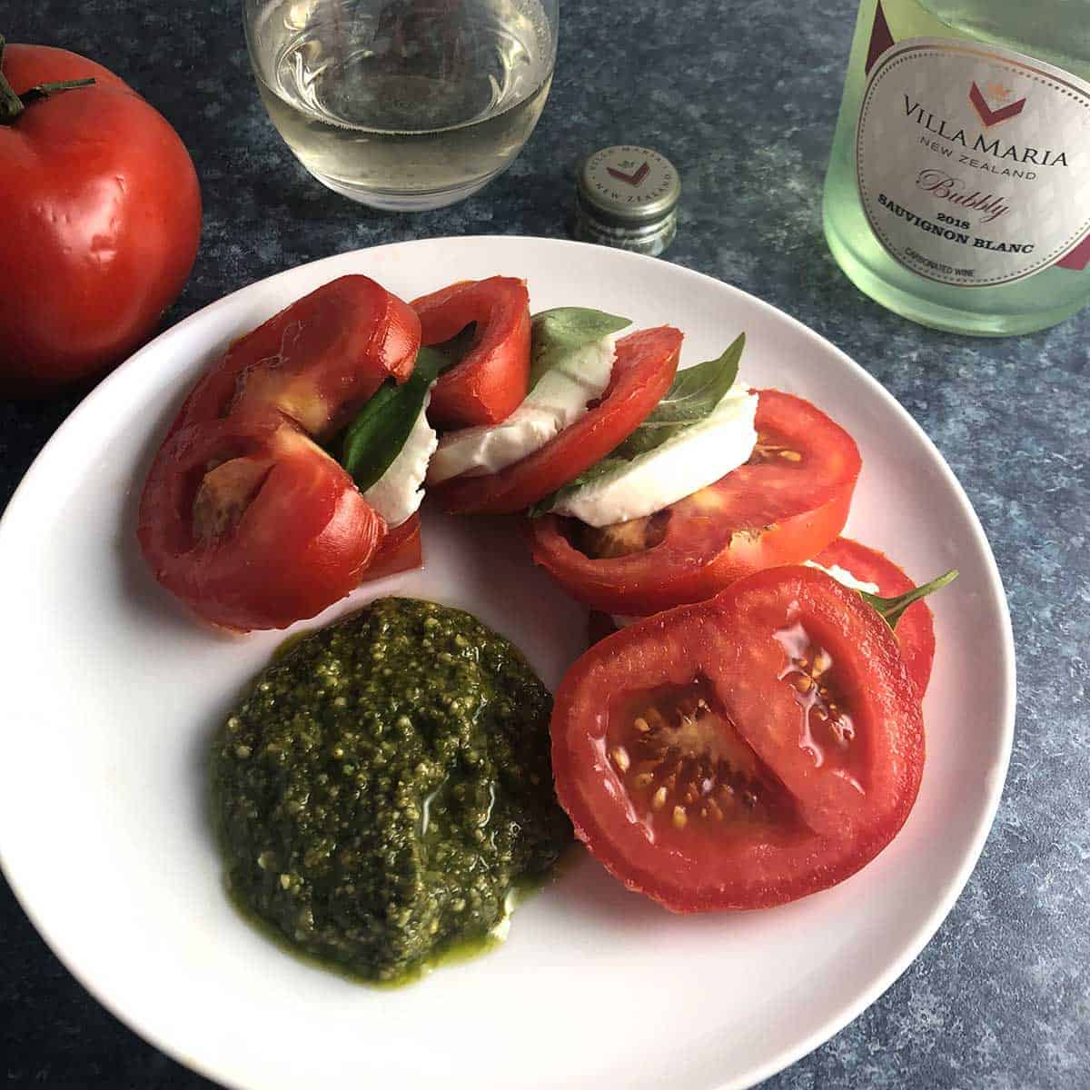 tomato caprese salad plated with pesto.
