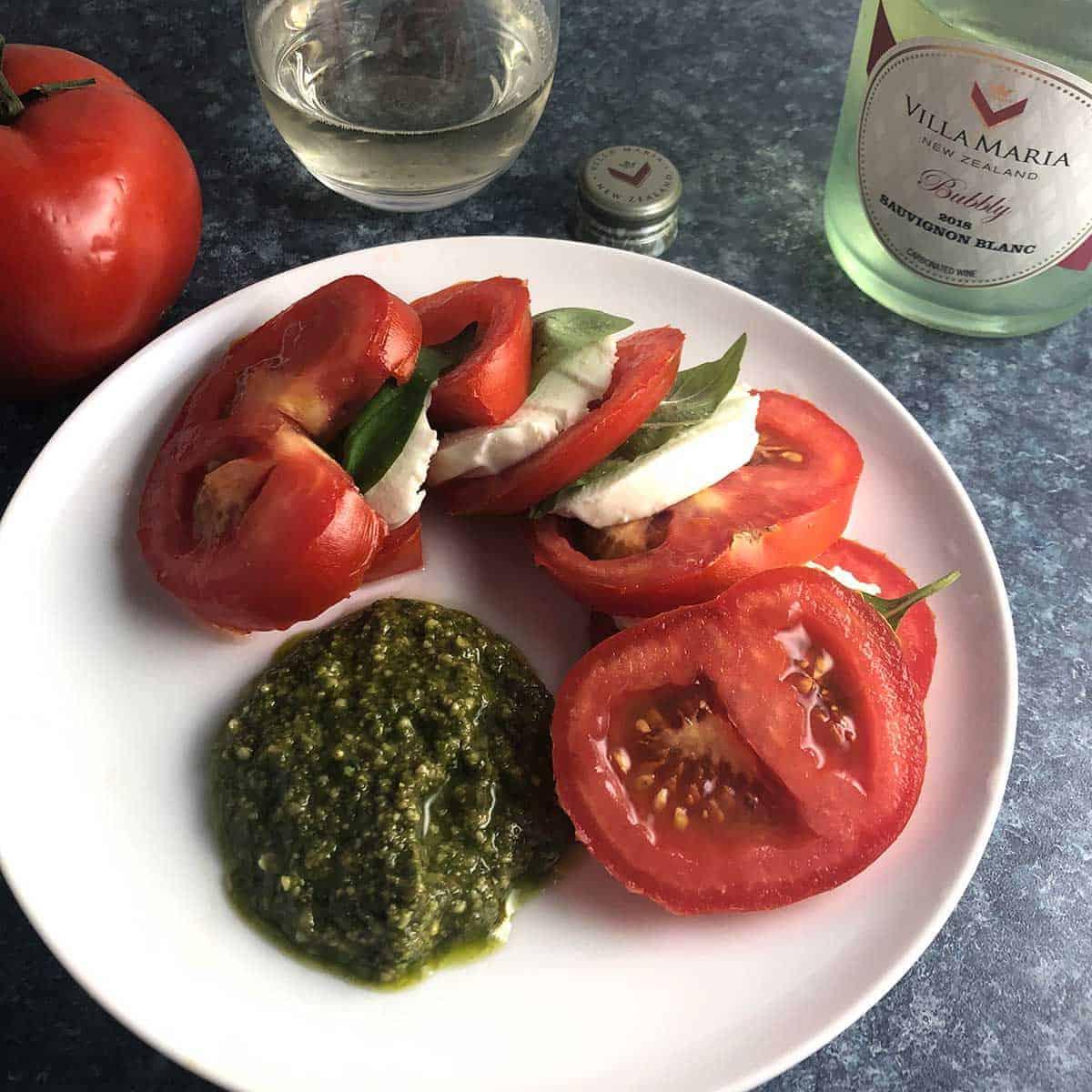 tomato caprese salad plated with pesto.