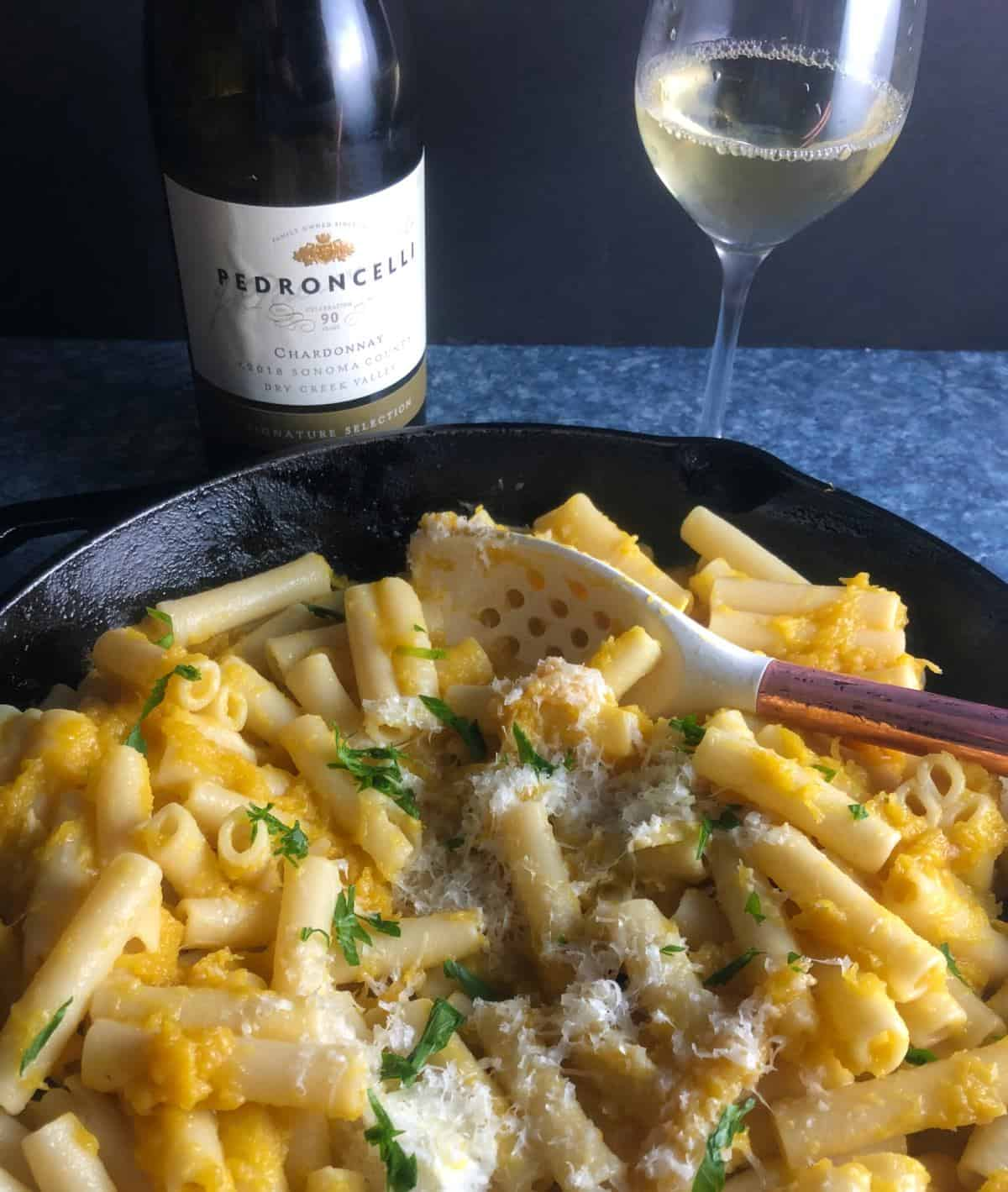 acorn squash pasta in a cast iron skillet along with a bottle and glass of Chardonnay white wine.