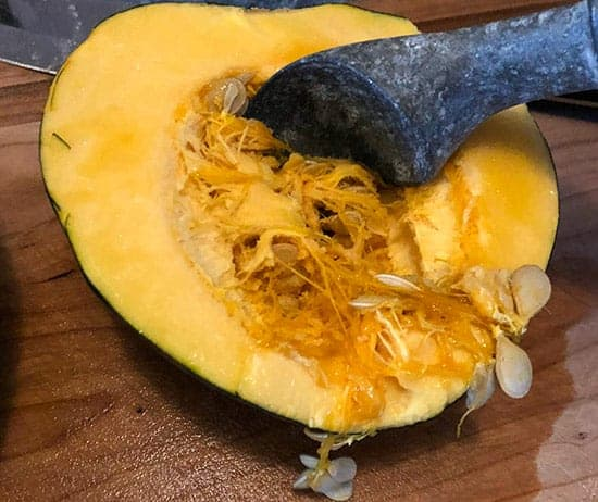 scooping seeds from an acorn squash