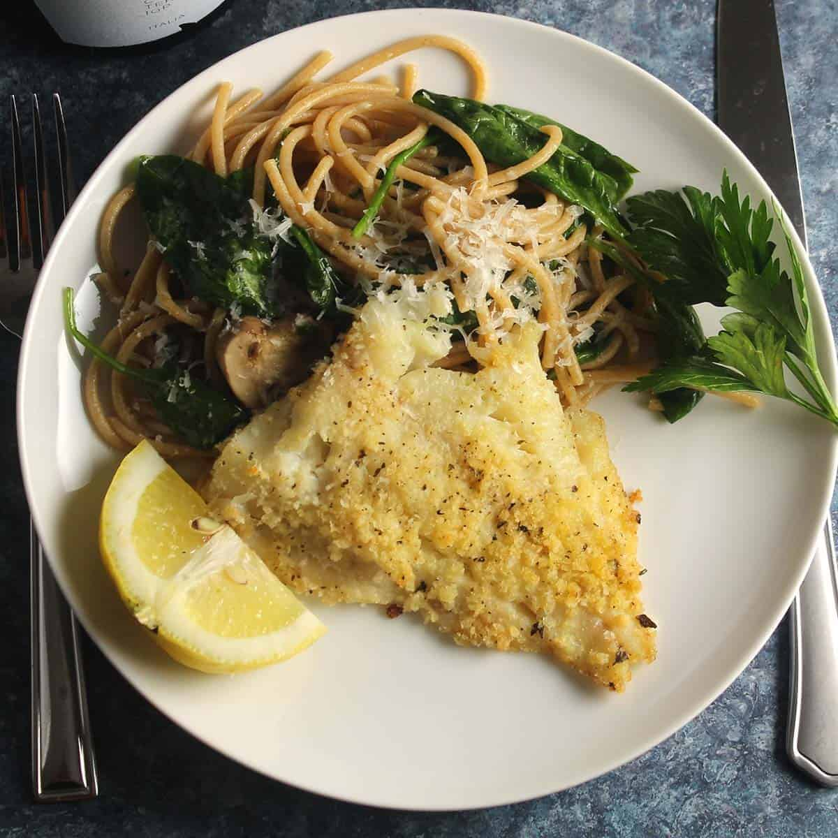 baked haddock on a plate with pasta.