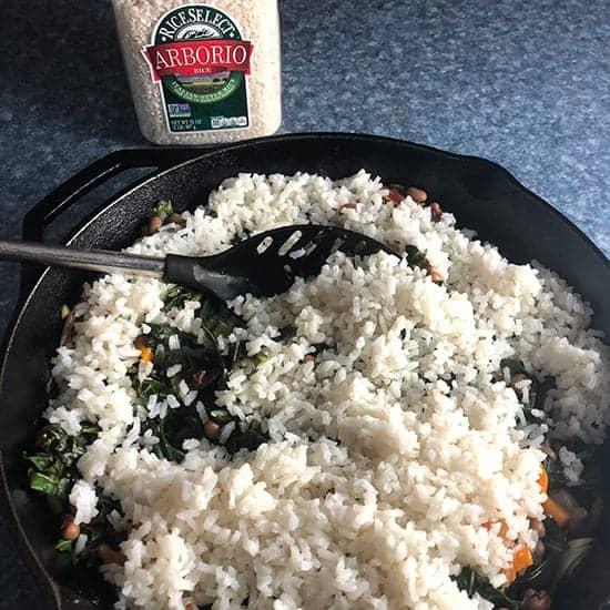 adding arborio rice to skillet.