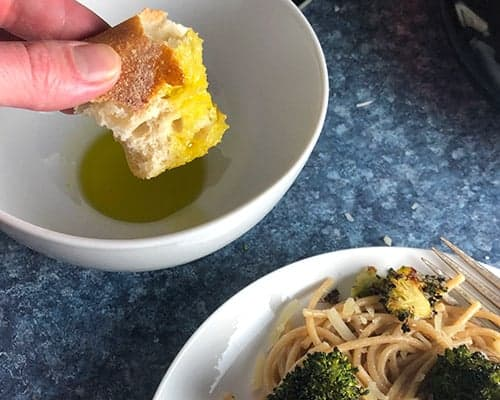 dipping bread into extra virgin olive oil
