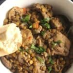 chicken and lentil stew in a bowl, with a piece of bread.