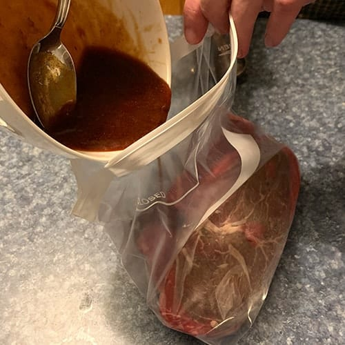 pouring marinade into bag with steak.