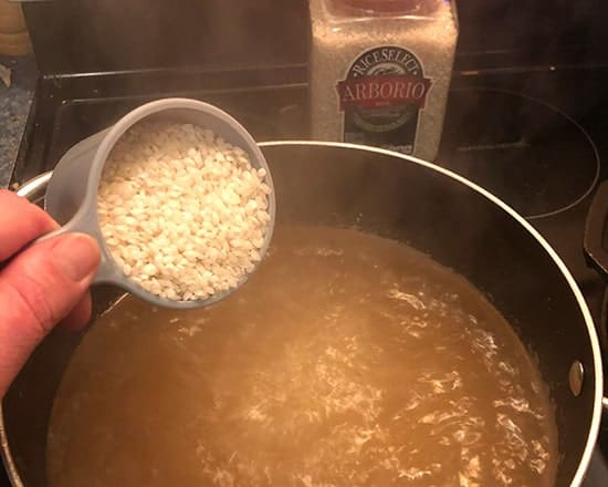 adding RiceSelect Arborio Rice to boiling water.