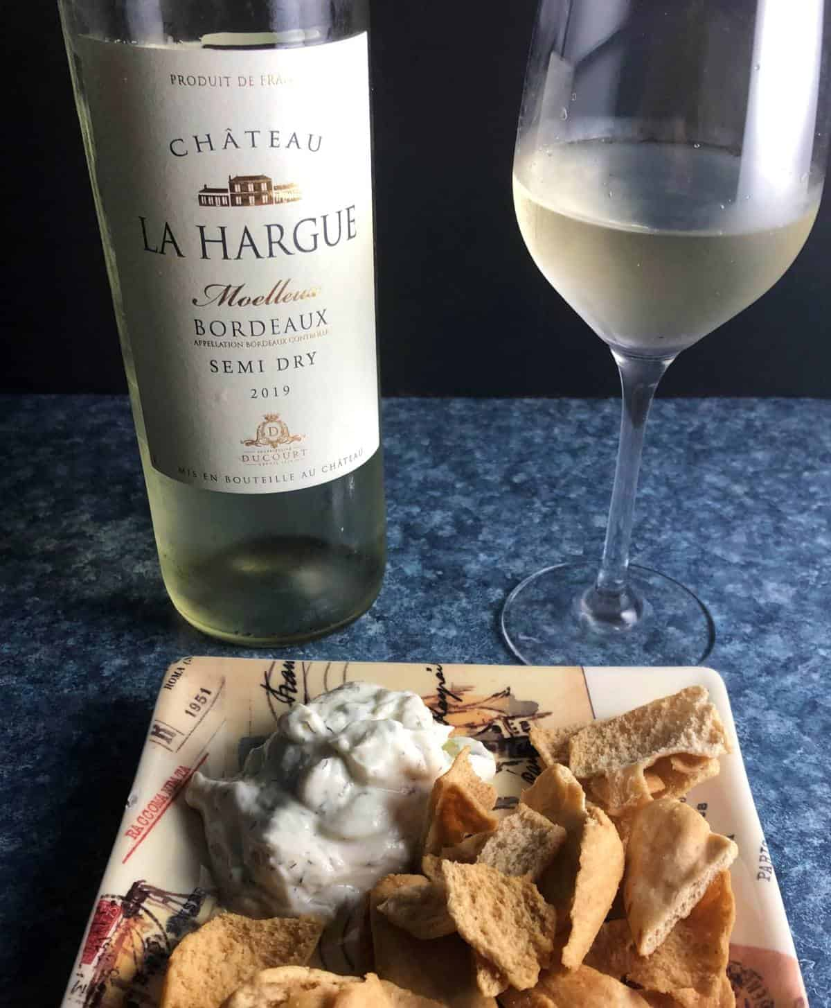 Bottle of Sweet Bordeaux wine served with tzatziki dip and pita chips.