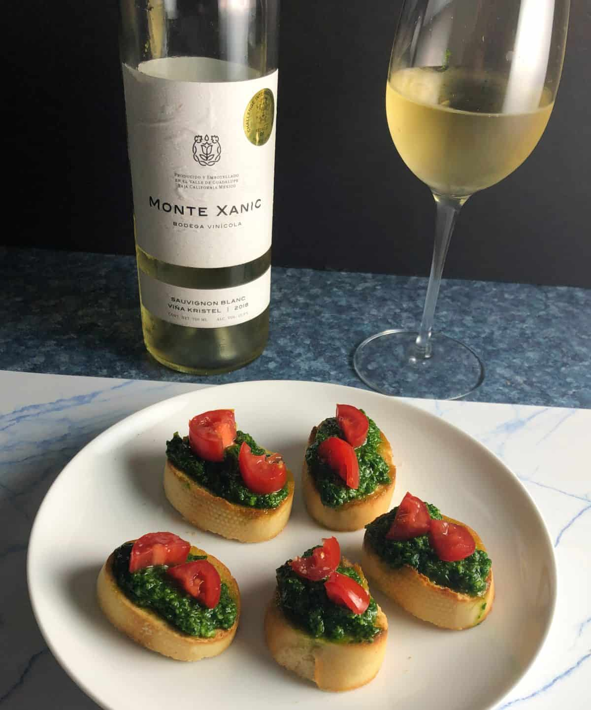 crostini topped with pesto and tomatoes, served with a white wine