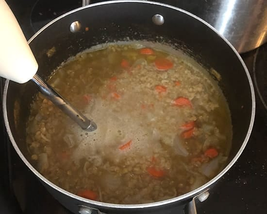 pureeing lentil soup with a handheld blender.