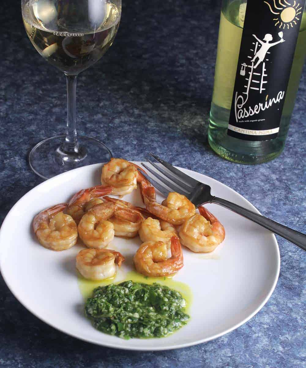 shrimp plated with cilantro sauce, served with white wine.