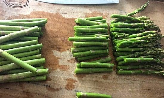 chopping asparagus on cutting board.