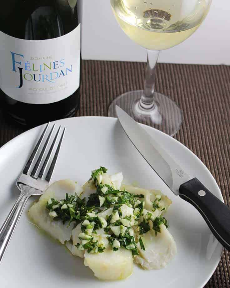 roasted cod with pesto served with white wine.