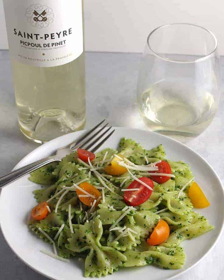kale pesto pasta with a bottle of Picpoul