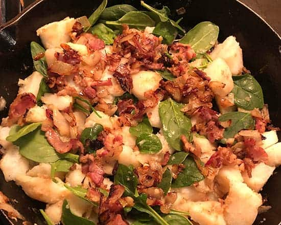 potatoes, bacon and spinach in a skillet.