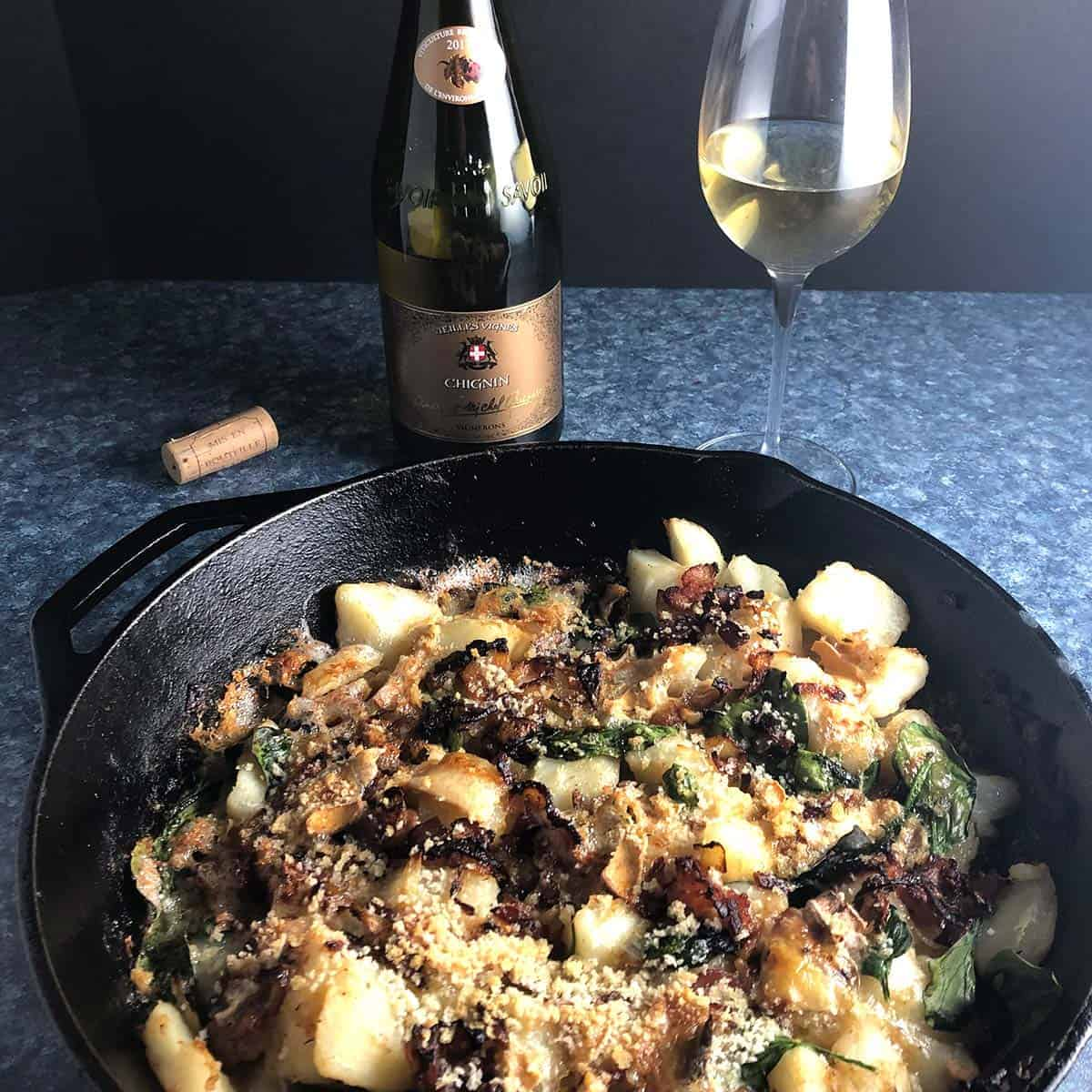 tartiflette in a skillet paired with wine.