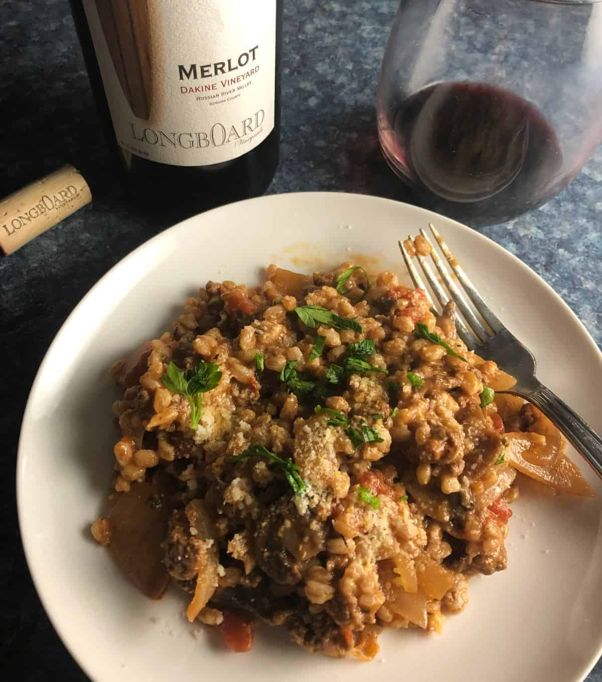 mushroom farro with ground beef on a white plate, served with red wine.