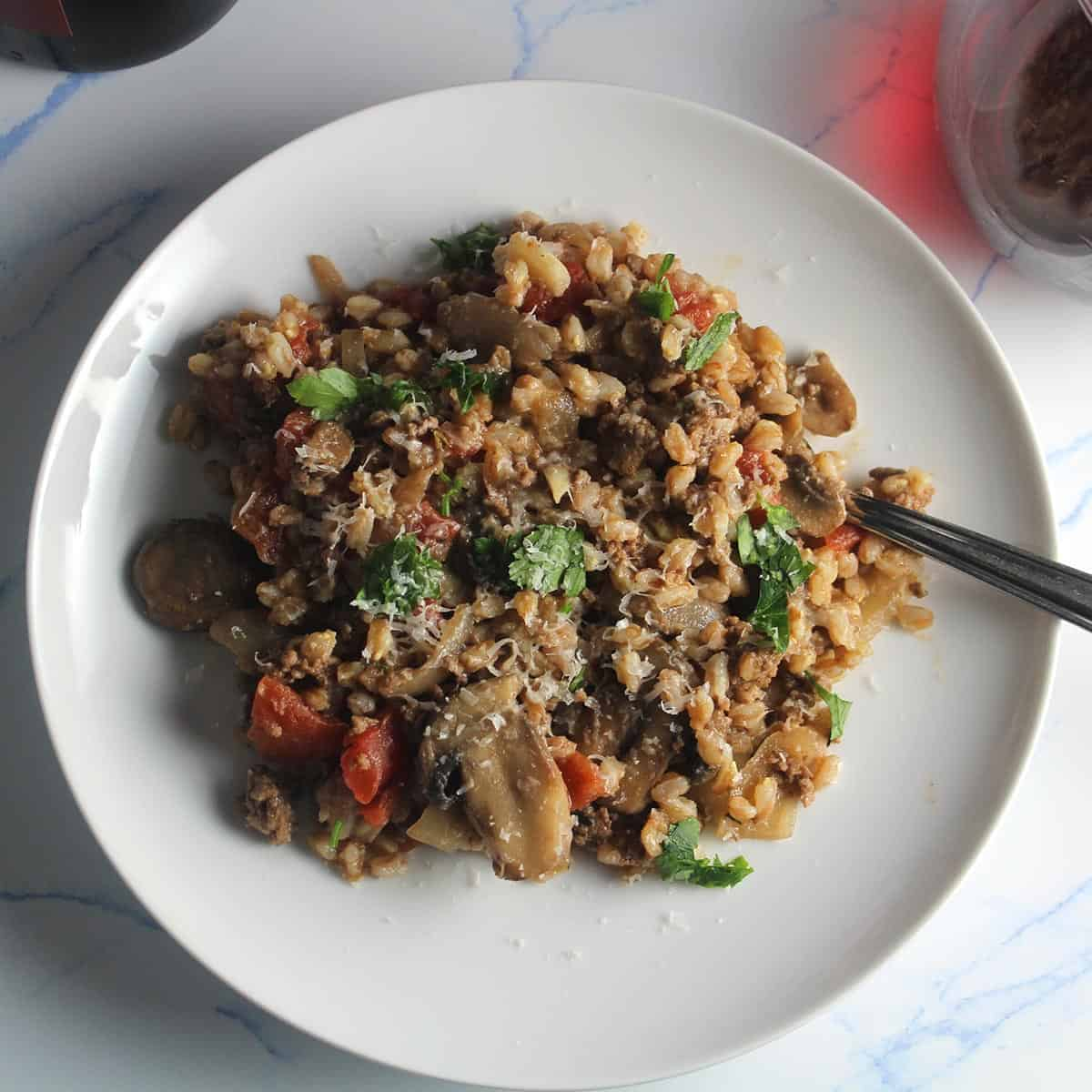 farro with mushroom and ground beef on a white plate