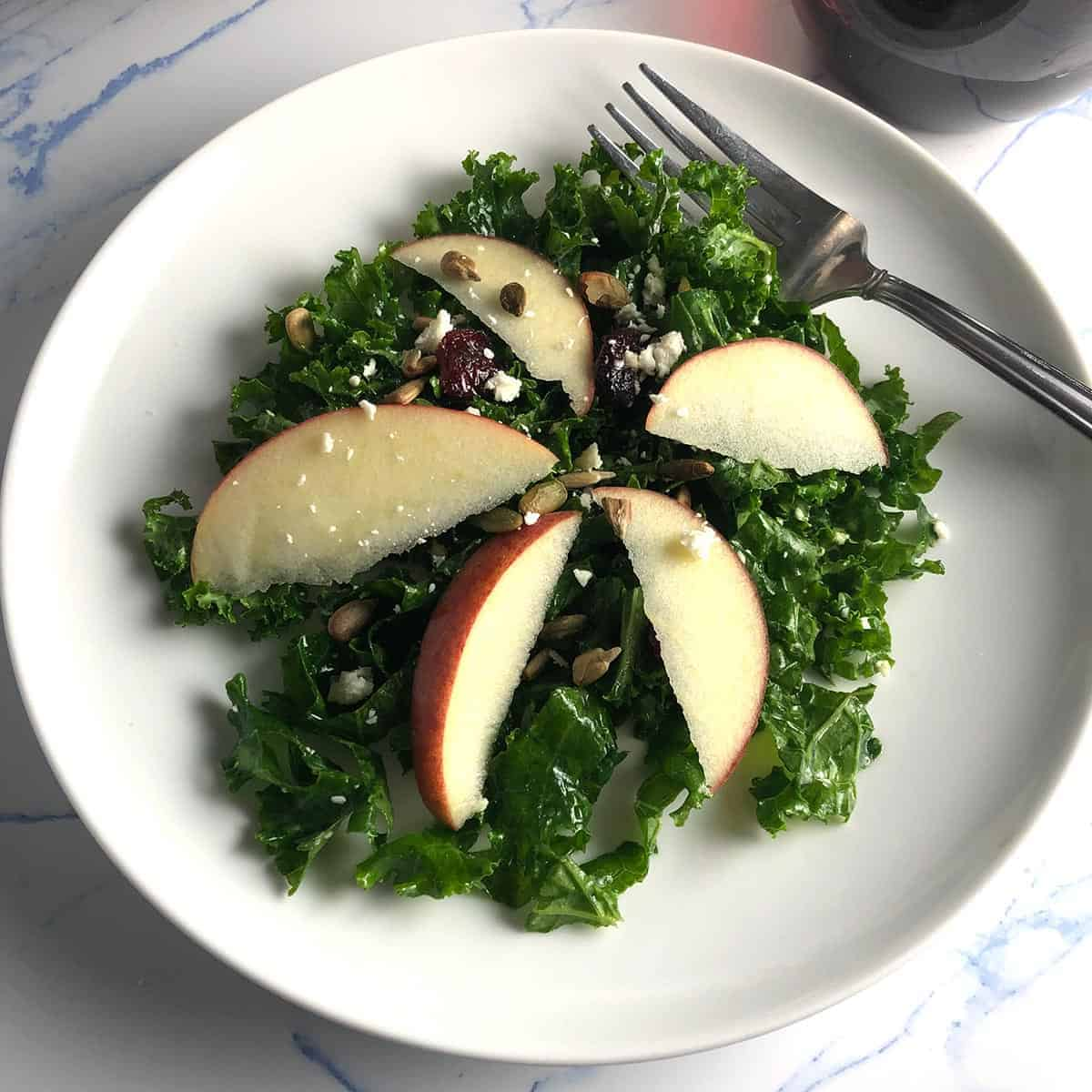 kale and apple salad served on a white plate.