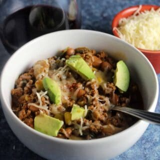 bowl of ground beef chili topped with avocado and cheese.