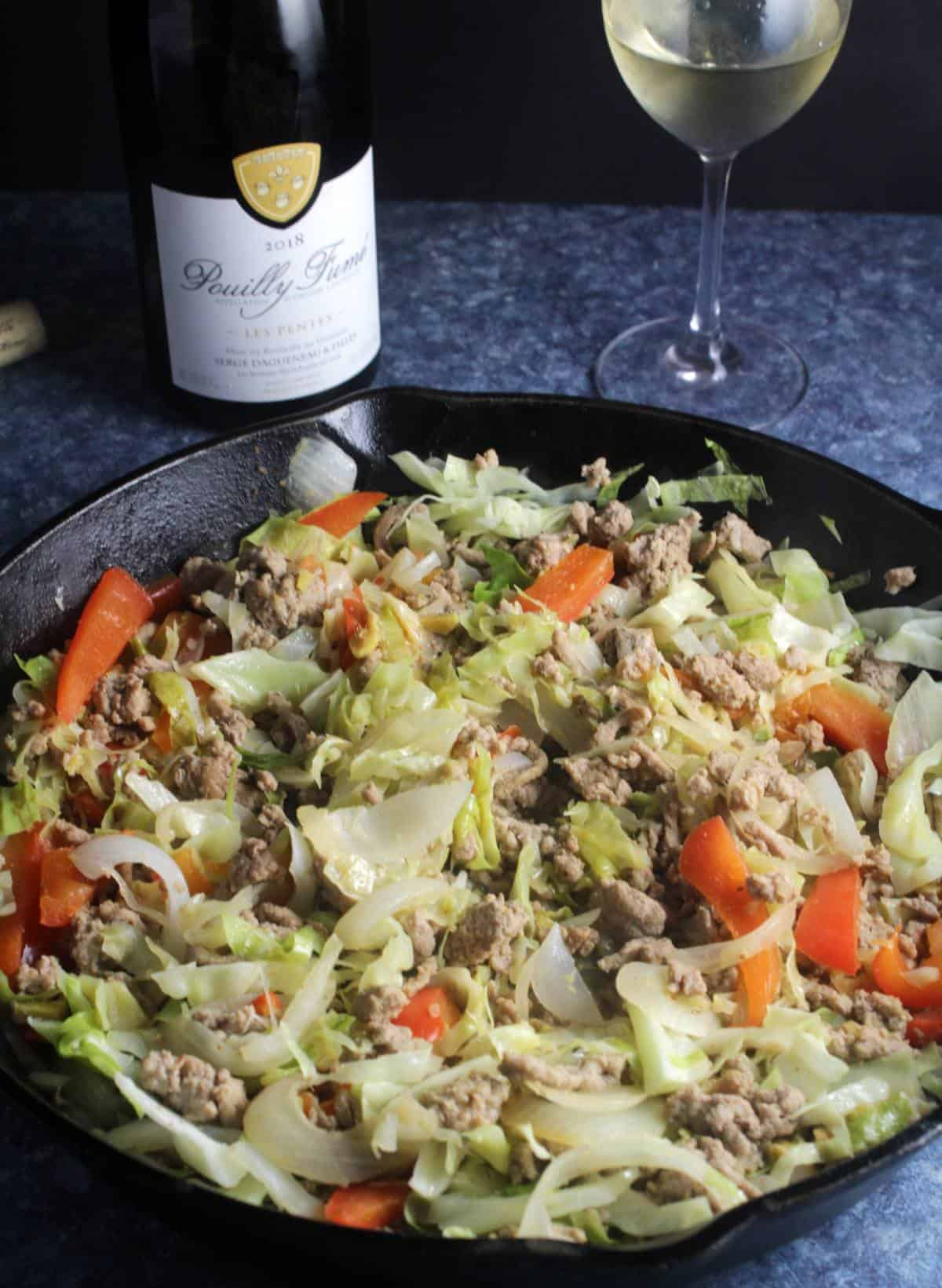 turkey and cabbage in skillet with bottle of wine.