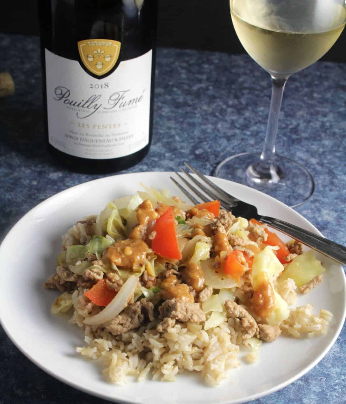 turkey cabbage stir-fry plated and served with white wine.