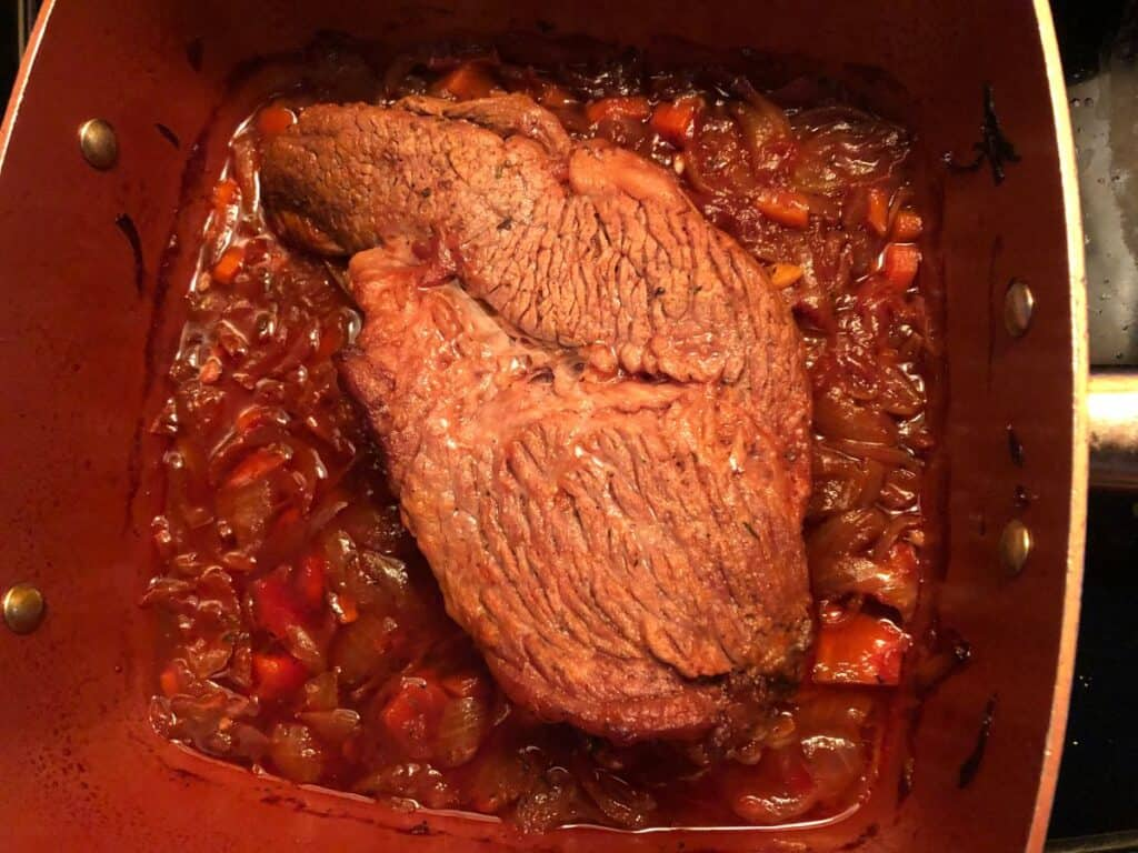 small brisket cooking in a copper pan.
