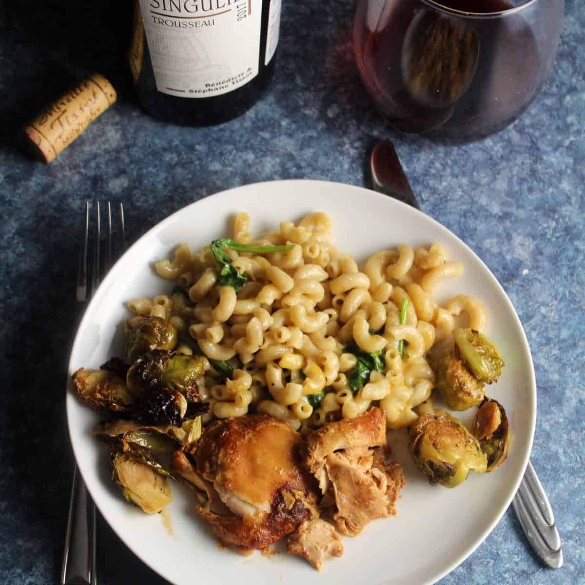 slow cooker BBQ chicken thights served with baked pasta, Brussels sprouts and red wine.