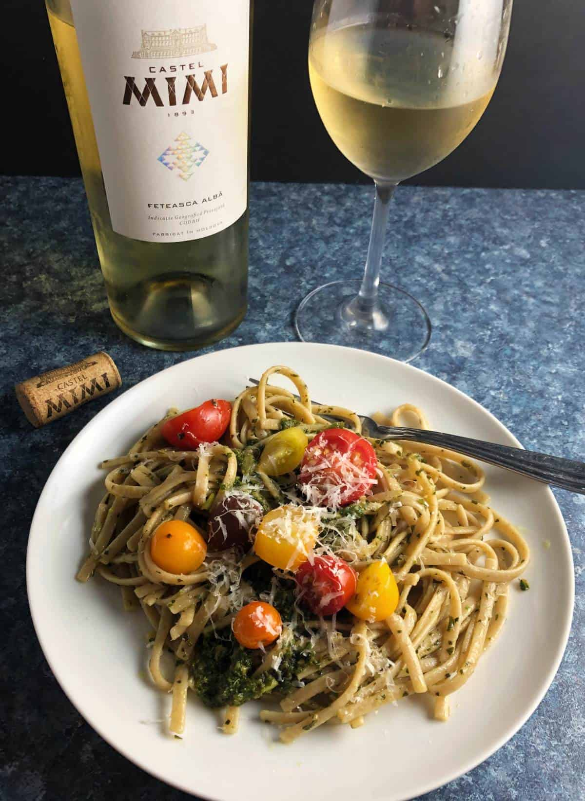 pasta with pesto topped with tomatoes served with a white wine.