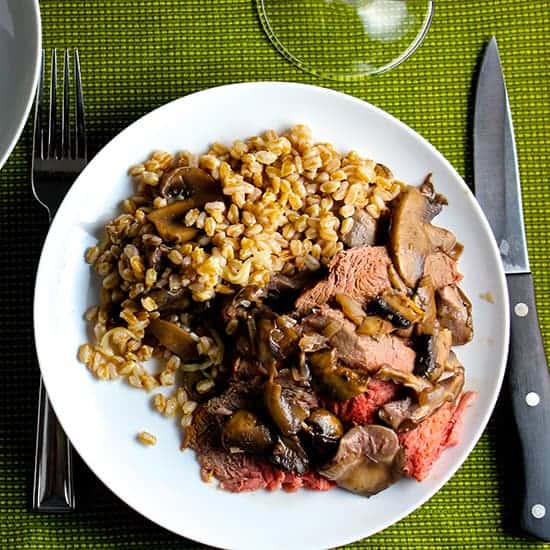 spoon roast with mushrooms and farro on a white plate.