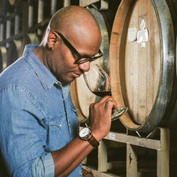 André Hueston Mack sampling wine with barrels behind him.