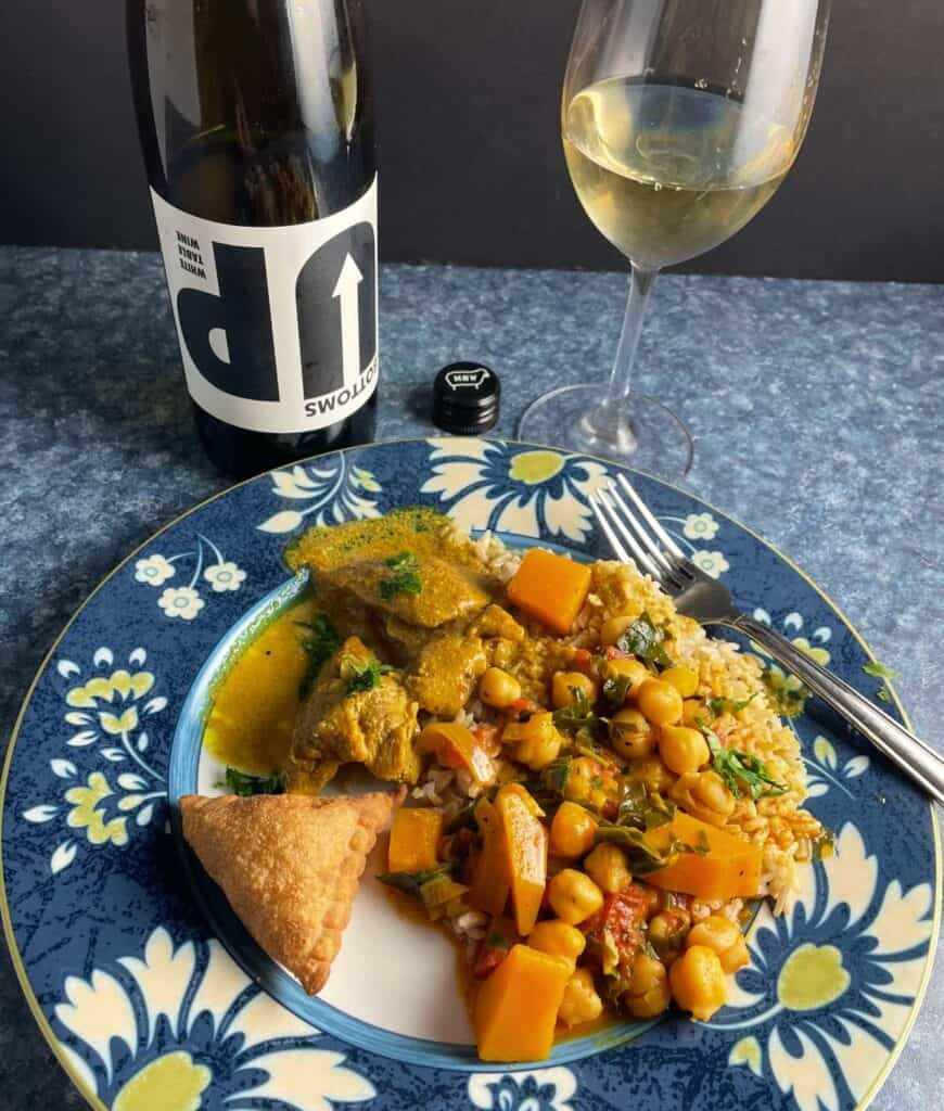 Indian food on a plate with Bottoms Up white wine.