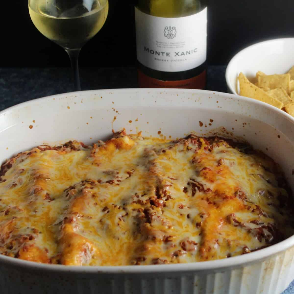 turkey enchiladas topped with sauce and melted cheese, in a baking dish with white wine in the background.